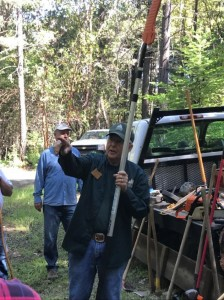 Bill Potterf describes the removal of ladder  trees while holding a large pole-saw.
